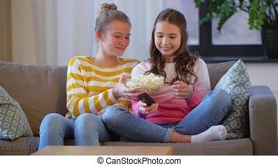 teenage girls eating popcorn watching tv at home - people, ...