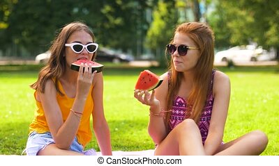 teenage girls eating watermelon at picnic in park - leisure...