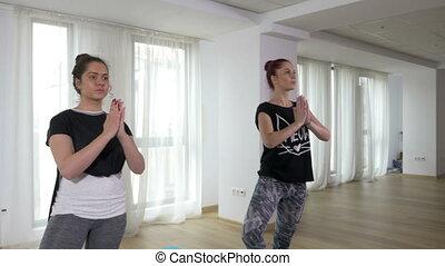 Teenage girls learning yoga with teacher