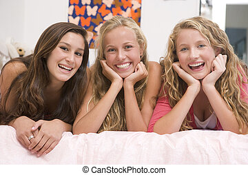 Teenage Girls Lying On Bed Using Mobile Phone