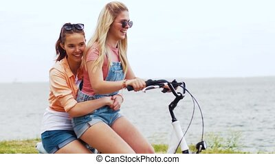 teenage girls or friends riding bicycle in summer