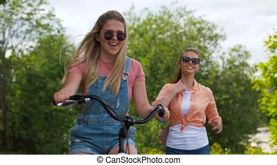 teenage girls or friends with bicycle in summer