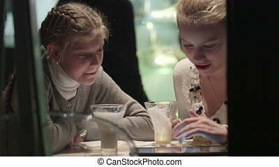 Teenage girls seen through the night window of coffee shop