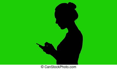 Teenage girl's silhouette with smartphone on green background