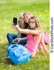 Teenage girls sitting on grass and taking selfie with mobile...