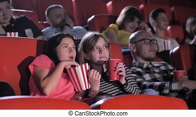 Diverse audience watching thrilling film at cinema. Cute teen schoolgirls enjoying interesting movie, drinking soda and eating popcorn, without taking their eyes off screen