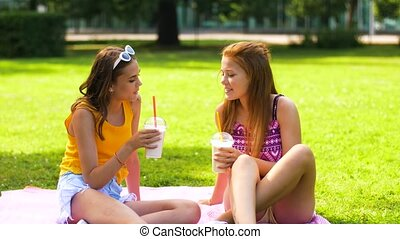 teenage girls with milk shakes at picnic in park - leisure...