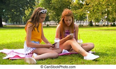 teenage girls with smartphones and shakes in park - leisure,...