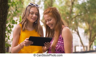 teenage girls with tablet pc in summer park - technology,...