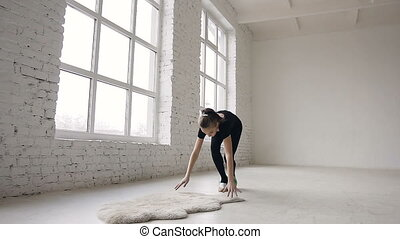 Teenage gymnast girl with the ball in his hands performs acrobatic moves at sport indoor in the white background near big windows