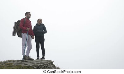 Teenage hiking couple in love kissing on the top of foggy mountain admiring the nature