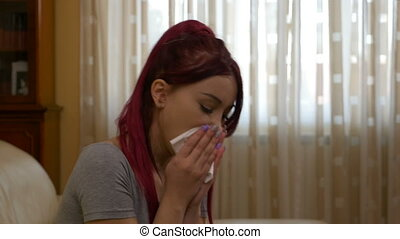 Teenage ill girl sneezing having a cold grabbing her sore throat and blowing nose in tissue