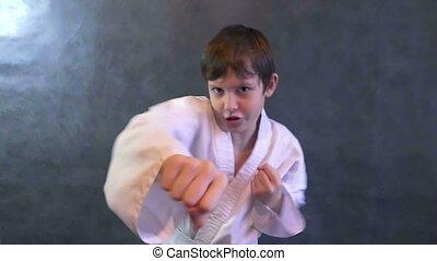 teenage karate boy in kimono fight hands waving fists slow motion