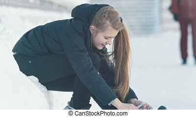 Teenage longhaired girl sitting on snow tightening the laces...