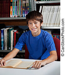 Teenage Male Student Sitting At Table In Library