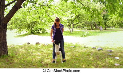 A teenage girl is training her dog in the fresh air. the dog stands on the feet of the mistress and they walk together. Animal trust. Animal training in a park under a tree surrounded by white stones