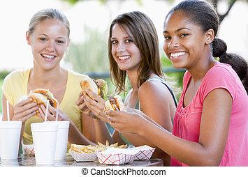 teenage piger, siddende, udendørs, nydelse, hurtig mad