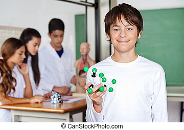Teenage Schoolboy Holding Molecular Structure In Biology Class