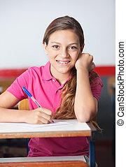 Teenage Schoolgirl Writing At Desk