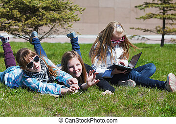 Teenage schoolgirls lying on a grass