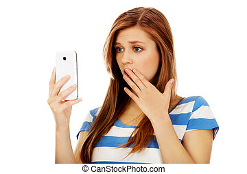 Teenage shocked woman reading a message on mobile phone