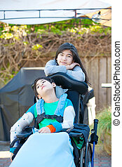 Teenage sister taking care of disabled brother in wheelchair outdoors
