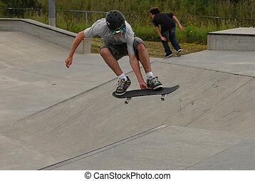 teenage skateboarder wearing helmet doing a roast beef out...