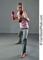 Teenage sportive girl is doing exercises with dumbbells to develop with dumbbells muscles on grey background. Sport healthy lifestyle concept. Sporty childhood. Teenager exercising with weights.