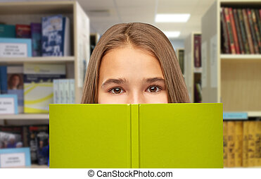 teenage student girl hiding over book at library