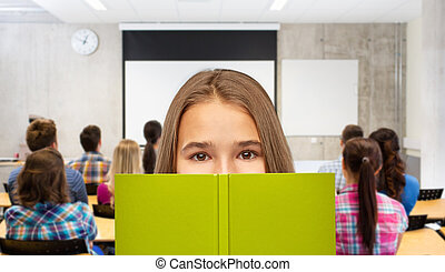 teenage student girl hiding over book at school