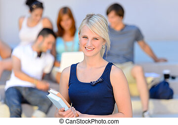 Teenage student girl smiling friends in background