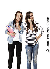 teenage student showing thumb up while her frind is on the phone on white background