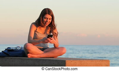 Teenage student texting at sunset on the beach - Happy...