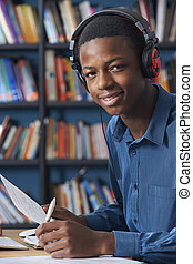 Teenage Student Wearing Headphones Whilst Working In Library