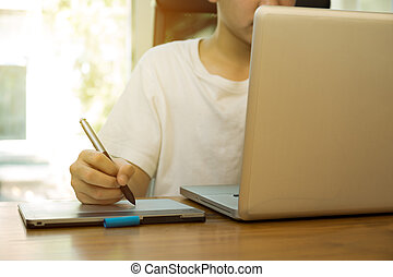 Teenage student working on laptop on wooden table