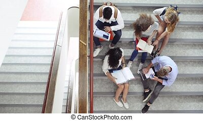 Teenage students on stairs in high school. - Group of...