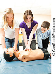 Teenage Students Practicing CPR - Two teenage girls and a...