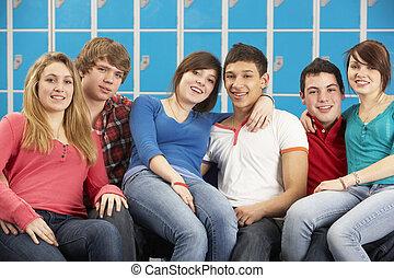 Teenage Students Relaxing By Lockers In School