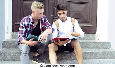 Teenage students sitting on stone steps in front of...
