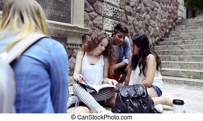 Teenage students sitting on the ground in front of university.