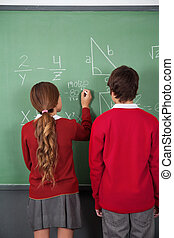 Teenage Students Solving Mathematics On Board