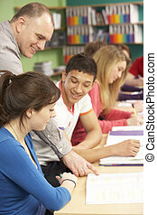 Teenage Students Studying In Classroom With Tutor