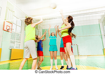 Teenage volleyball players striking ball over net - Low...