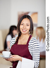 Teenage Waitress Holding Coffee Cup In Cafe
