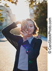Teenage with retro camera on city street
