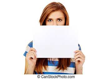 Teenage woman covering face with blank card
