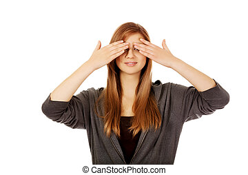 Teenage woman covering her eyes with both hands