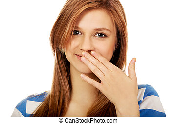 Teenage woman giggles covering her mouth with hand