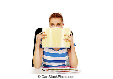 Teenage woman hiding her face behind a notebook