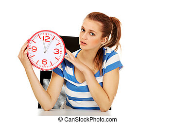 Teenage woman looking at clock